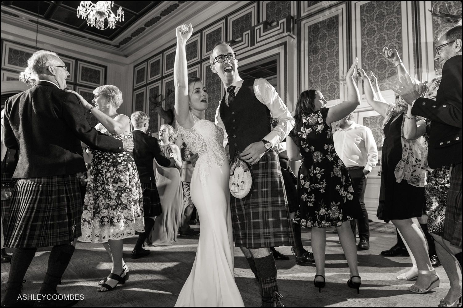 Bride and groom cheering on dance floor