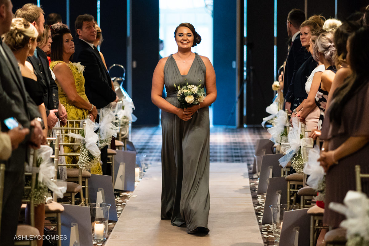 Bridesmaid comes down aisle