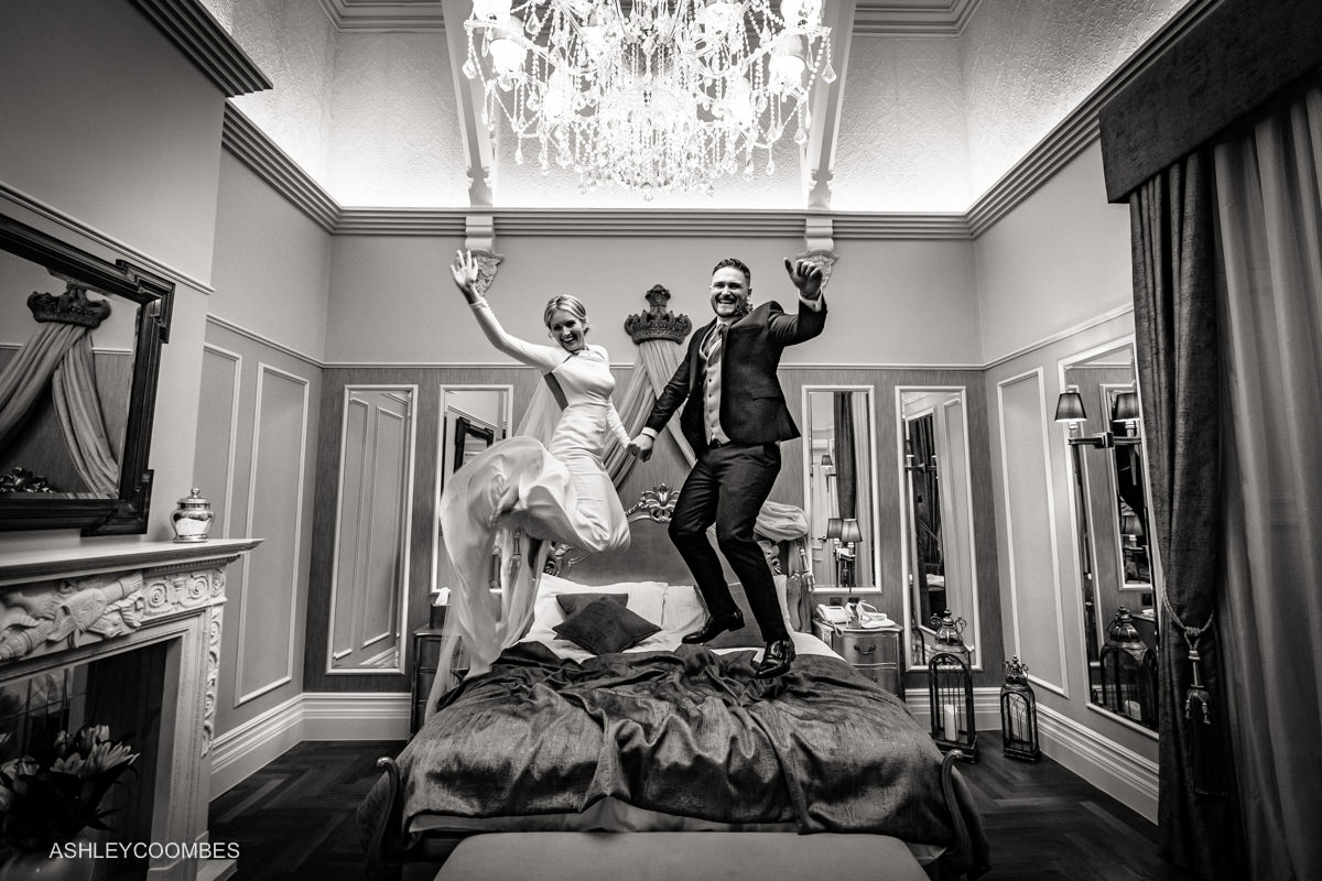 bride and groom bouncing on bed