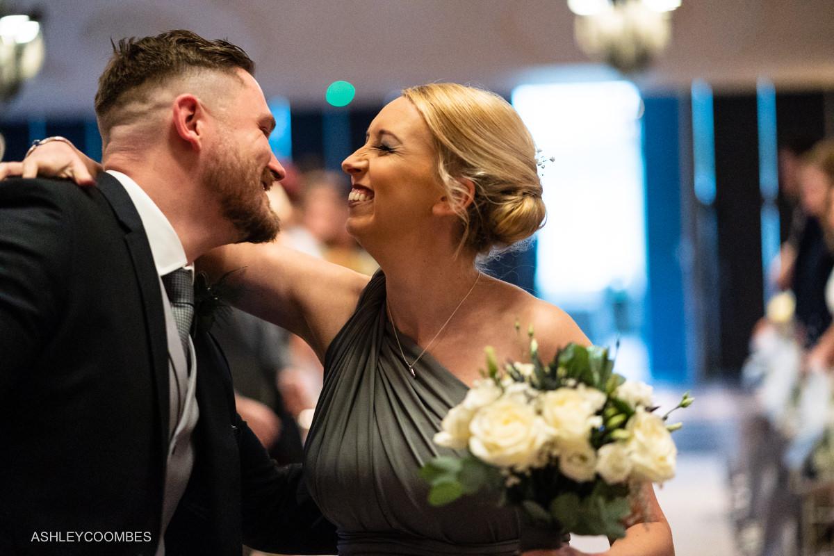 bridesmaid kisses groom
