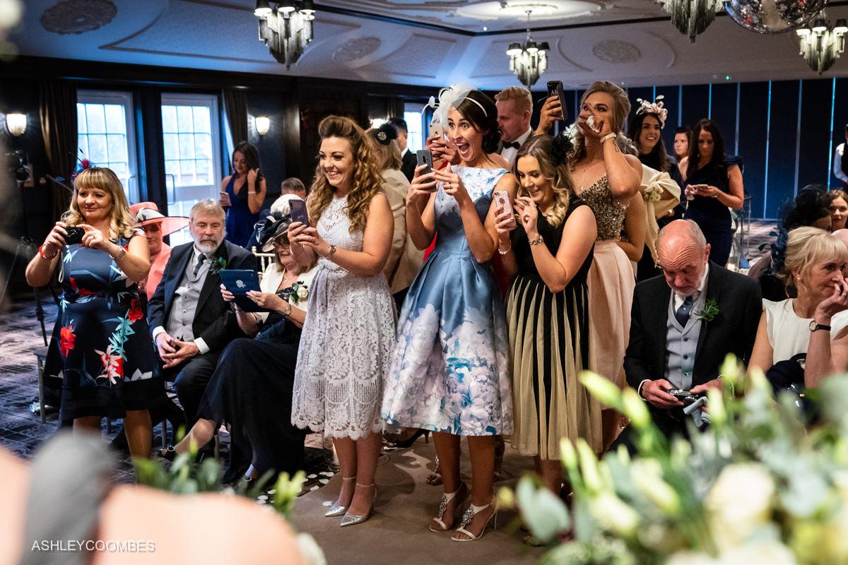 wedding guests use phone cameras